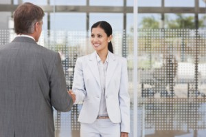 Happy young Asian business woman shaking hands with a male associate outside