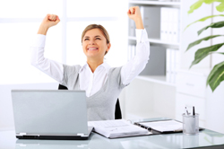 Successful businesswoman raising hands and laughing sitting on workplace.